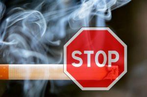 Znak stop, a za nim tlący się papieros.