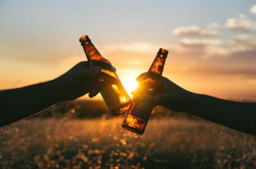 dwie ręce stukające się butelkami od piwa